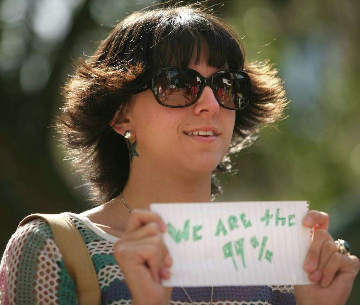 Ashley Jade of Bridgeport holds up a sign during an Occupy Wall Street type protest outside 10 Middle Street in downtown Bridgeport on Tuesday, October 11, 2011.