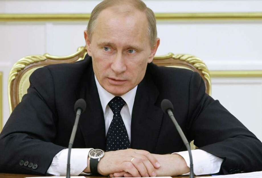 "Russian Prime Minister Vladimir Putin chairs a Cabinet meeting in Moscow, Tuesday, Jan. 25, 2011. Putin vowed ""retribution is inevitable"" for the suicide bombing that killed dozens of people at Russia's busiest airport, while President Dmitry Medvedev demanded robust checks at all transport hubs and lashed out at the airport for lax security. (AP Photo/RIA Novosti, Alexei Nikolsky, Pool) Photo: Alexei Nikolsky / POOL RIA NOVOSTI"