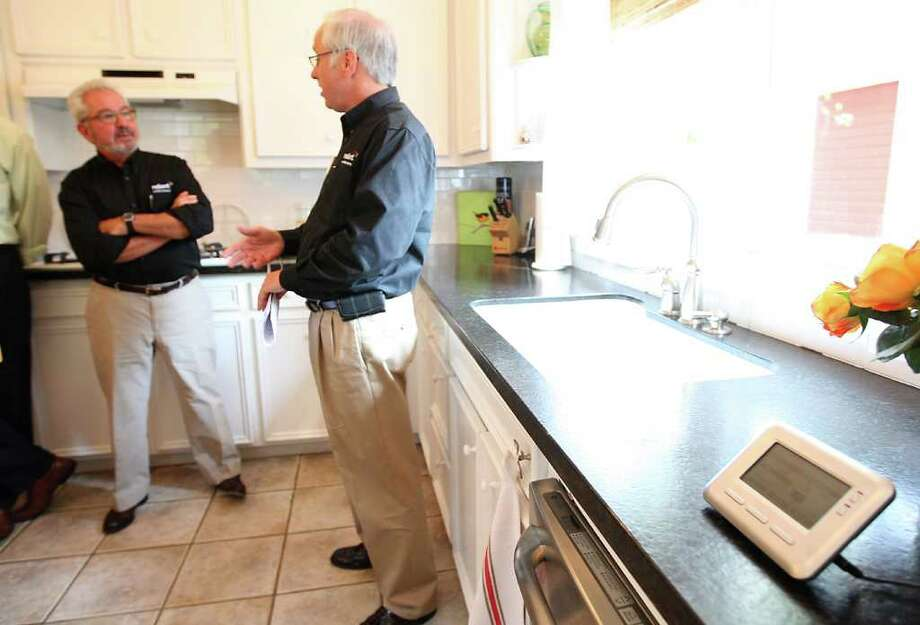 Karen Warren Photos : Chronicle ELECTRICITY IN THE AIR: Home improvement expert Bob Vila, left, talks Tuesday with Reliant Energy's Wayne Morrison in a house in the Sixth Ward, just west of downtown. On the counter in the foreground is a home energy monitor. Photo: Karen Warren / © 2011 Houston Chronicle