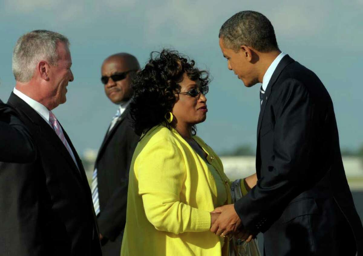 President Barack Obama greets Rep. Corrine Brown, D-Fla., center, as Orlando Mayor Buddy Dyer, left, looks on after arriving at Orlando International Airport in Orlando, Fla., to attend two fundraisers, Tuesday, Oct. 11, 2011. (AP Photo/Susan Walsh)