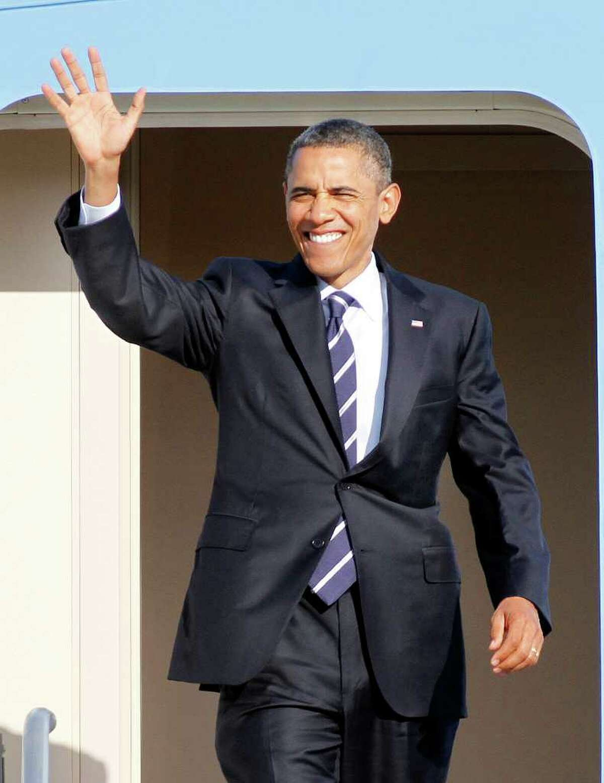 President Barack Obama waves from the stairs of Air Force One after arriving in Orlando, Fla., Tuesday, Oct. 11, 2011. (AP Photo/Reinhold Matay)