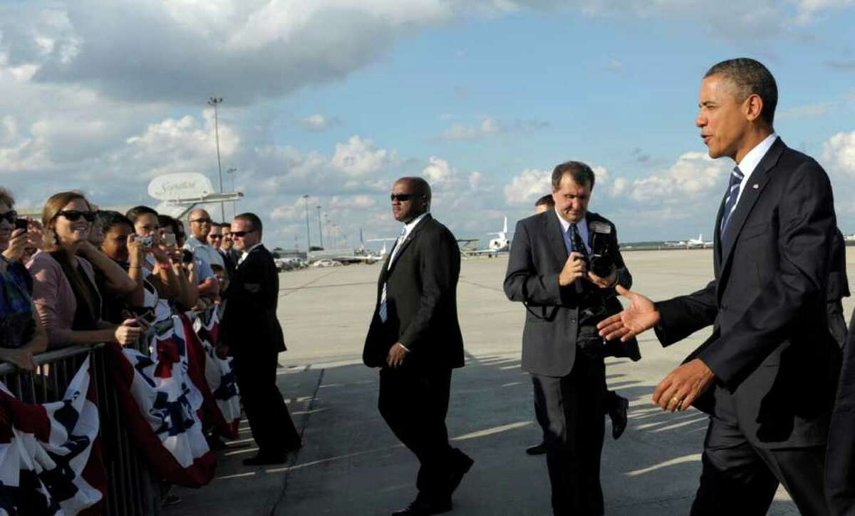 President Barack Obama walks to greets people after arriving at Orlando International Airport in Orlando, Fla., to attend two fundraisers, Tuesday, Oct. 11, 2011. (AP Photo/Susan Walsh)