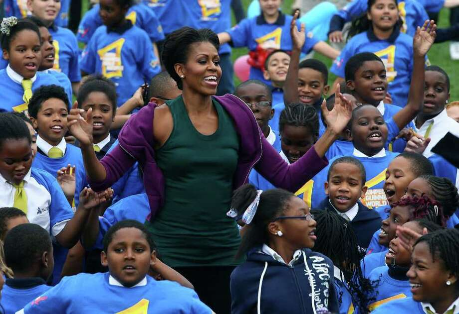 MARK WILSON : GETTY IMAGES  JUMP START:  First lady Michelle Obama does jumping jacks with 400 schoolchildren on the South Lawn of the White House on Tuesday in a bid to break the Guinness record. Photo: Mark Wilson / 2011 Getty Images