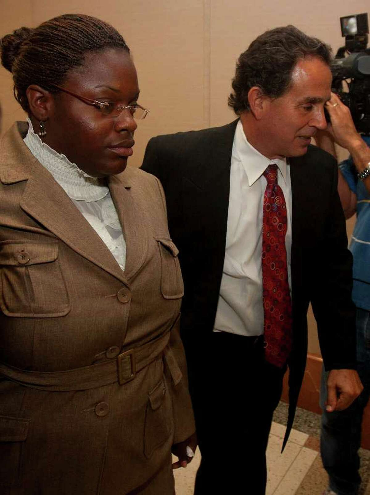 Tyonne Palmer (left) leaves the courtroom with her lawyer Anthony Osso (right) after testifying in the capital murder case of Pastor Tracy Bernard
