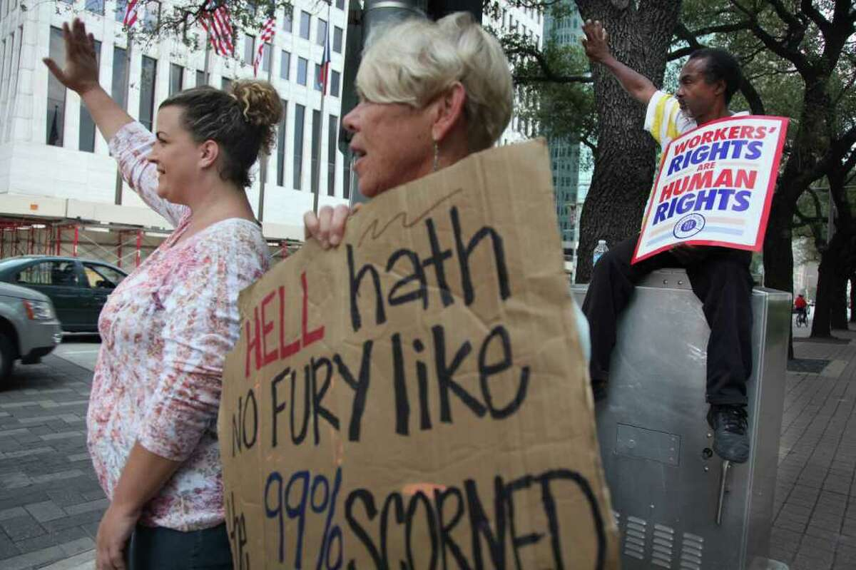 Shere Dore, 35, of Houston, cheers as cars honk in approval as a small group of Occupy Houston protesters gather at City Hall on Tuesday, Oct. 11, 2011, in Houston. ( Mayra Beltran / Houston Chronicle )