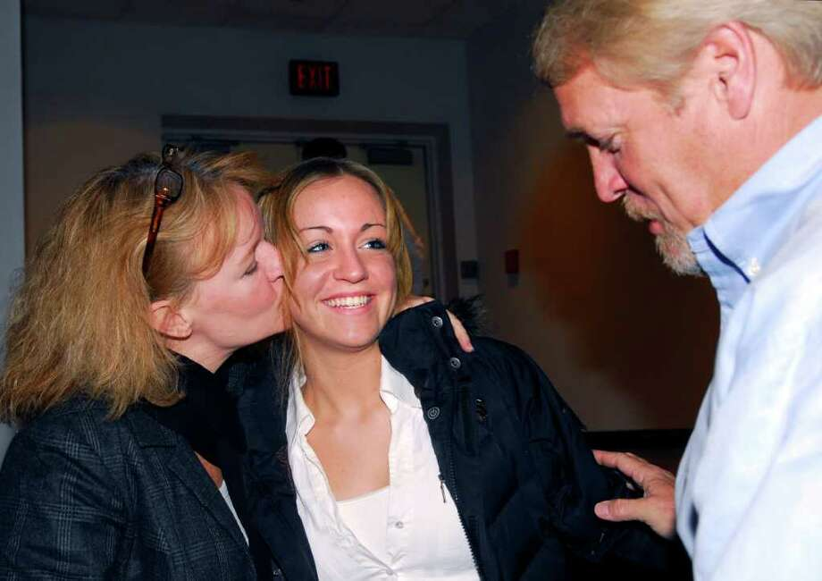 Sandi Curley, left, gives her daughter, Kelsey Curley, 18, a kiss, just after Kelsey graduated during the mid-year graduation ceremony at Greenwich High School on Jan. 24, 2008. At right is Kelsey's father, Michael Curley. Kelsey Curley was found dead in her home on Monday, Oct. 10, 2011. Photo: Bob Luckey , GT / Greenwich Time