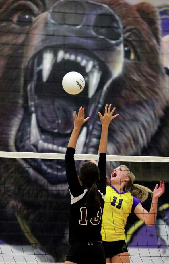 Montgomery's Rachael Harvey (11) lifts the ball over Magnolia's Morgan Miller (13) during Montgomery High School's 3-2 win over Magnolia High School Tuesday, Oct. 11, 2011, in Montgomery. Photo: Johnny Hanson, Houston Chronicle / © 2011 Houston Chronicle