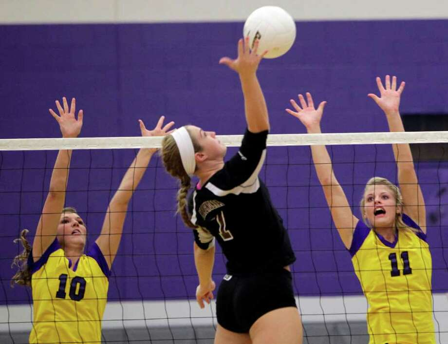 Montgomery's Rachael Harvey (11) and Taryn Driver (10) look to block the ball from Magnolia's Madison Butler (7) during Montgomery High School's 3-2 win over Magnolia High School Tuesday, Oct. 11, 2011, in Montgomery. Photo: Johnny Hanson, Houston Chronicle / © 2011 Houston Chronicle