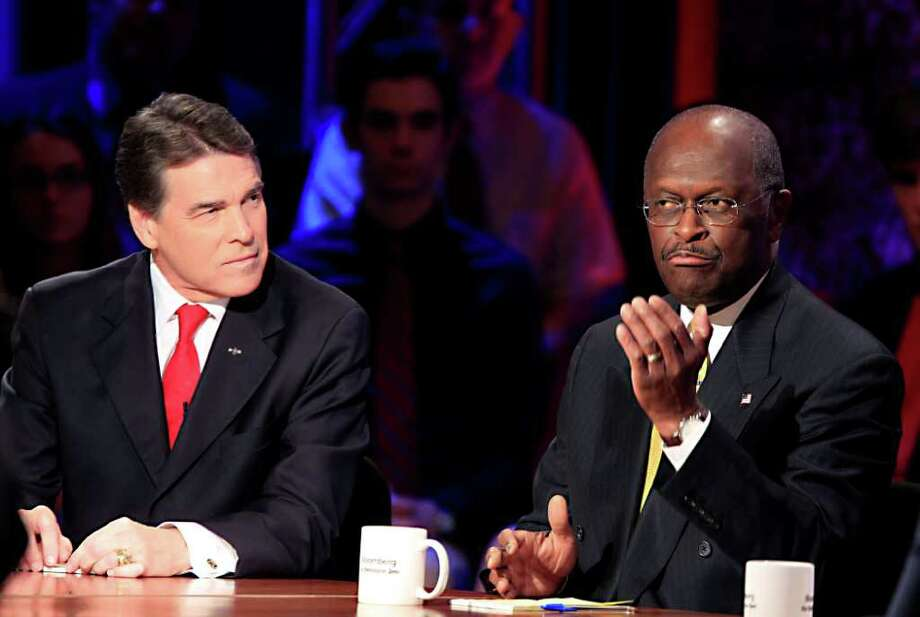 ANDREW HARRER : BLOOMBERG '9-9-9': Texas Gov. Rick Perry listens as Herman Cain, right, makes a point during Tuesday's GOP  presidential debate. Cain and frontrunner Mitt Romney dominated the night. Photo: Andrew Harrer / © 2011 Bloomberg Finance LP