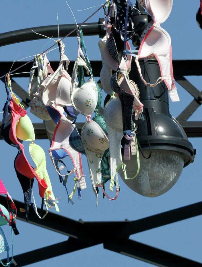 A portion of the bras hung across the Hot Metal Bridge over the Monongahela River are seen below the superstructure of the bridge Wednesday, Oct. 5, 2011. Aerie, a bra company that's part of Pittsburgh-based American Eagle Outfitters, has a current breast cancer campaign: where this steel bridge in the city has been draped in thousands of bras, to heighten breast cancer awareness awareness. Aerie said $1 from every sale during October will be donated to a breast cancer charity, up to $50,000. (AP Photo/Keith Srakocic) Photo: Keith Srakocic