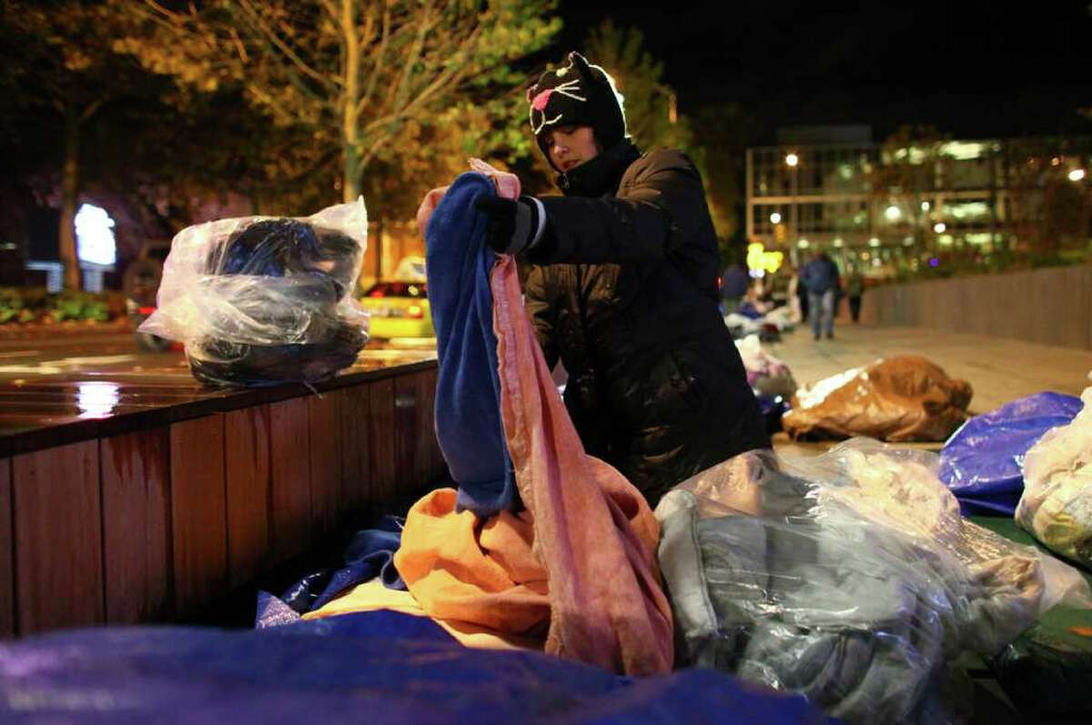A woman that goes by the name 'Spooky Kat' unpacks her belongings as homeless people and advocates prepare to sleep in front of the Bill & Melinda Gates Foundation.