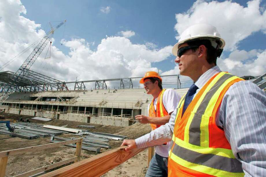Dynamo team president of business operations Chris Canetti, right, and Dynamo defender Bobby Boswell look over the Dynamo's new stadium under construction. Photo: James Nielsen, Chronicle / © 2011 Houston Chronicle
