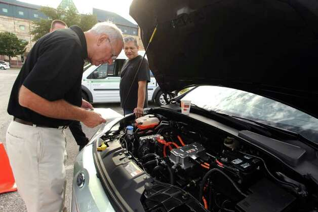 Phillip Fizzell, retired Ford engineer, examines a Ford Focus Electric which was on display, along with other Ford environmentally friendly vehicles, at the UTSA downtown campus on Tuesday, Oct. 11, 2011. The model soon will be available to the public. Photo: BILLY CALZADA, Billy Calzada/gcalzada@express-news.net / gcalzada@express-news.net