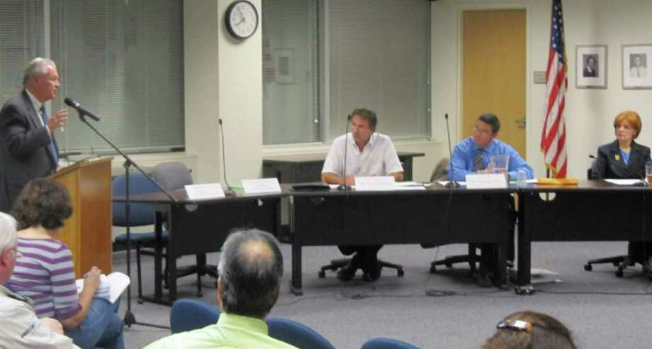 Interim First Selectman Michael Tetreau, left, addresses the Board of Education on Tuesday night, asking them to delay a vote on a memorandum of understanding on an employees' health reserve fund. Board members from left are: Paul Fattibene, Tim Kery and Catherine Albin. Photo: Kirk Lang / Fairfield Citizen