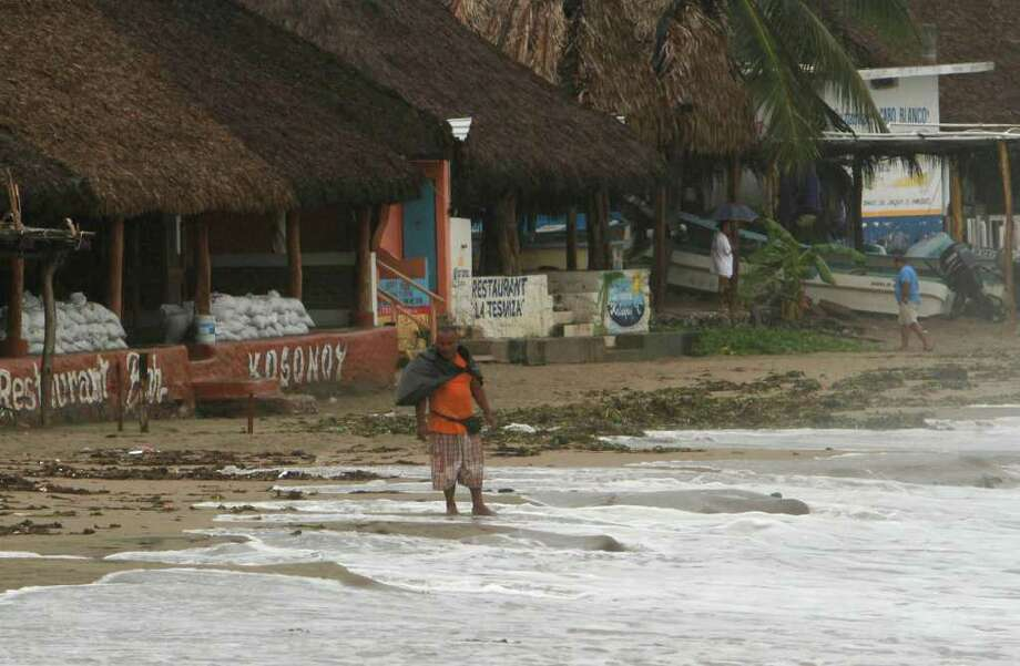 Beach-front restaurant owners, who say they will ride out the storm, pass the time before the anticipated arrival of Hurricane Jova in Melaque, Mexico on Tuesday Oct. 11, 2011. Jova weakened a little as it neared land, but it still had maximum sustained winds of 100 mph, the U.S. National Hurricane Center reported, forecast to make landfall between Barra de Navidad, near Melaque, and Puerto Vallarta late Tuesday. The owners say they are staying to protect their properties from thieves. Photo: AP