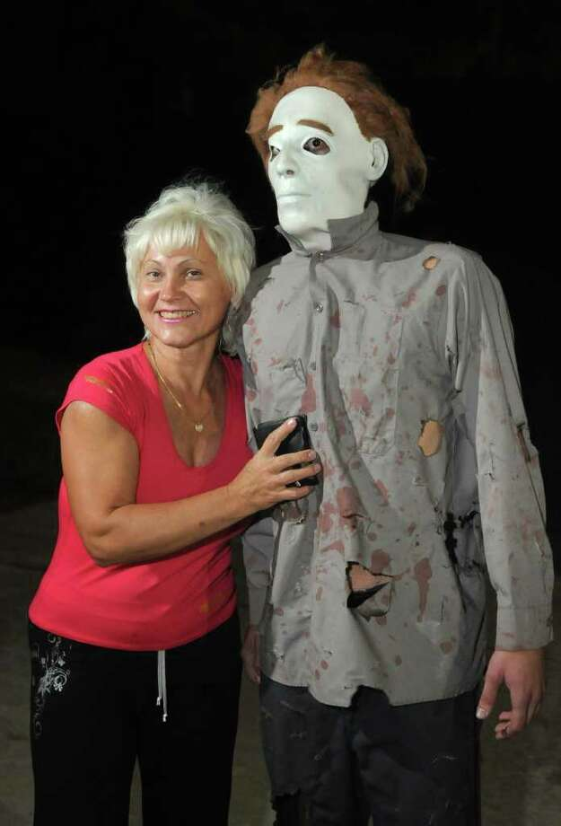"MASKED MAN: Larisa Khomenko visits with Alex Lazar, who plays the part of ""Michael Meyers""at The Kingwood Asylum. Photo: Jerry Baker"
