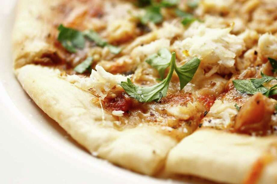 The new Gumbo Pizza sounds like it could be a mess, but it's a triumph: a yeasty, crisp crust swiped with an earthy brown roux and topped with lots of sweet, shreddy crab and mozzarella. Photo: Michael Paulsen / © 2011 Houston Chronicle