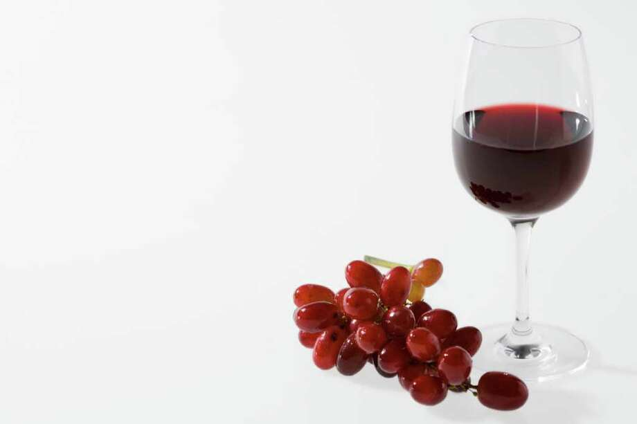Champagne bottles , red wine glass and grapes Photo: Polka Dot Images / handout