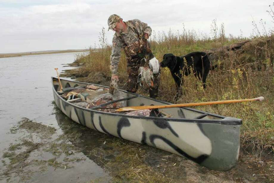 PRAIRIE PROVIDENCE - Mike Furtman loads his monring's take of ducks - mallards and canvasvback -into a canoe after a fine morning of waterfowling on a large, natural wetland in North Dakota. Photo: Shannon Tompkins