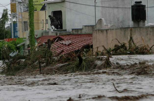Toppled trees are caught in flood waters of a main intersection in Villa de las Garzas, Mexico, Wednesday Oct. 12, 2011. Jova slammed into Mexico's Pacific coast as a Category 2 hurricane early Wednesday, swamping beach towns and causing floods in the mountains above before dropping to tropical storm force as it swept past Puerto Vallarta. Photo: AP