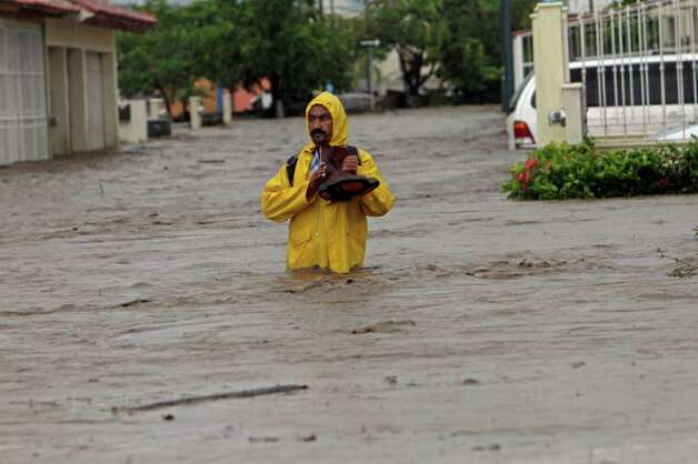 A man wades through a street flooded by the heavy rains dumped by Hurricane Jova in Villa de las  Garzas, Mexico, Wednesday Oct. 12, 2011. Jova slammed into Mexico's Pacific coast as a Category 2 hurricane early Wednesday, swamping beach towns and causing floods in the mountains above before dropping to tropical storm force as it swept past Puerto Vallarta. Photo: AP
