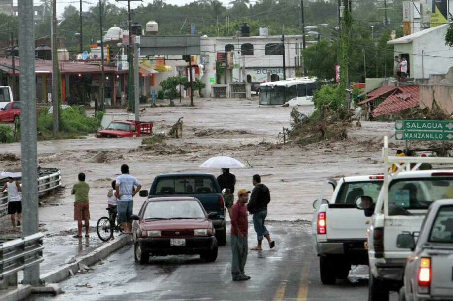 Residents stand at the edge of a main intersection inundated with flood waters and scattered with toppled trees and stranded vehicles in Villa de las Garzas, Mexico, Wednesday Oct. 12, 2011. Jova slammed into Mexico's Pacific coast as a Category 2 hurricane early Wednesday, swamping beach towns and causing floods in the mountains above before dropping to tropical storm force as it swept past Puerto Vallarta. Photo: AP