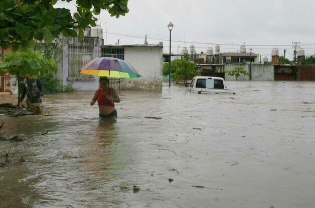 A woman wades through a street flooded by heavy rains dumped by Hurricane Jova in Villa de las  Garzas, Mexico, Wednesday Oct. 12, 2011. Jova slammed into Mexico's Pacific coast as a Category 2 hurricane early Wednesday, swamping beach towns and causing floods in the mountains above before dropping to tropical storm force as it swept past Puerto Vallarta. Photo: AP