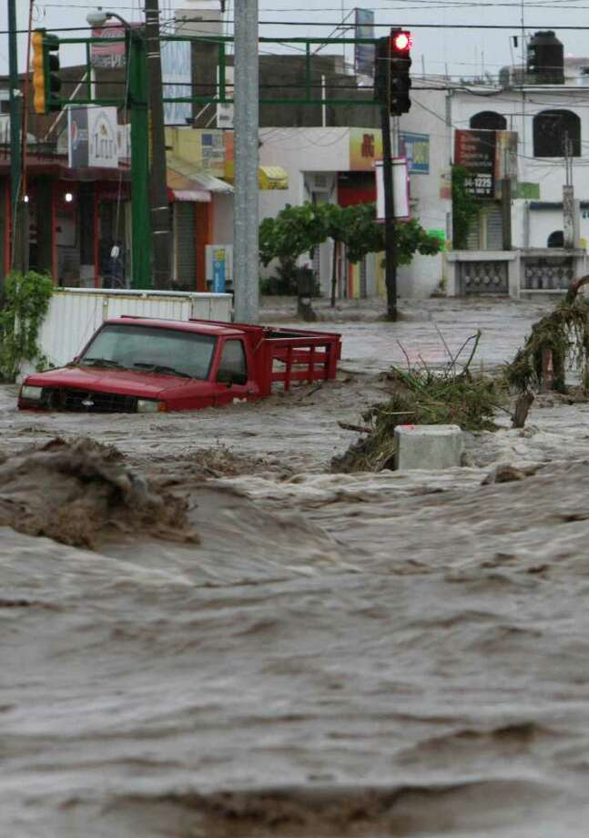 Toppled trees and a vehicle are caught in the flood waters of a main intersection in Villa de las Garzas, Mexico on Wednesday Oct. 12, 2011. Jova slammed into Mexico's Pacific coast as a Category 2 hurricane early Wednesday, swamping beach towns and causing floods in the mountains above before dropping to tropical storm force as it swept past Puerto Vallarta. Photo: AP