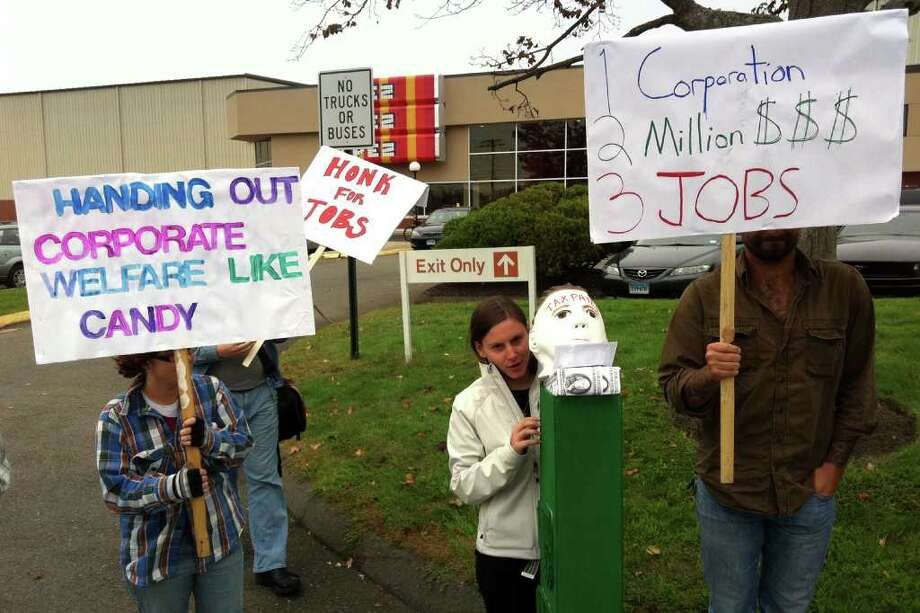 Elise Willer stands with her Pez dispenser Wednesday outside the Pez Candy factory in Orange protesting government loans to businesses. Photo: Rob Varnon