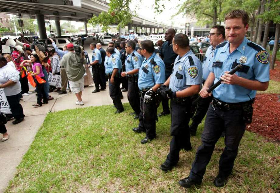 Police push people away from the Mickey Leeland Federal Building during a protest Wednesday, Oct. 12, 2011, in Houston. More than 200 protesters, some of whom went inside the building, rallied around the federal building in the Occupy Houston movement. Several who went inside and staged an impromptu sit in were arrested. Photo: Brett Coomer, Houston Chronicle / © 2011 Houston Chronicle