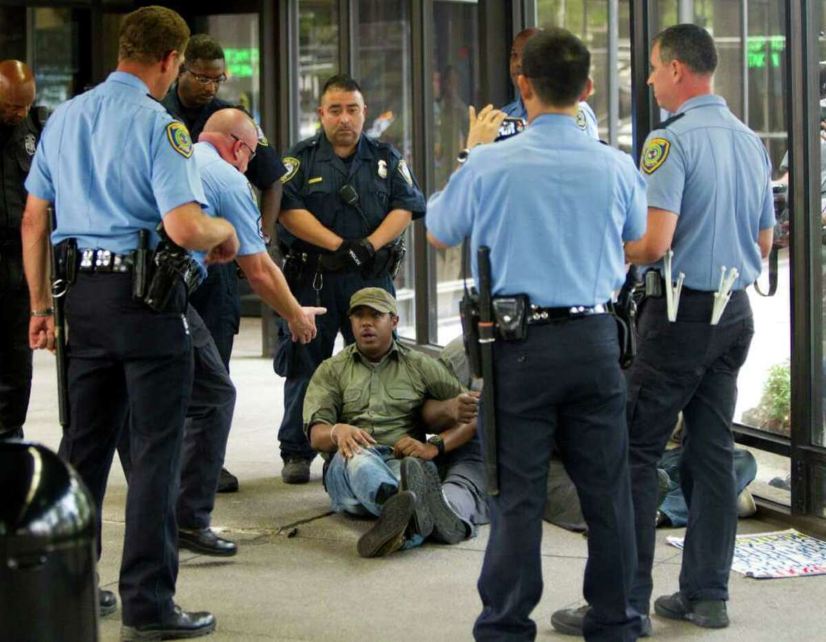 A demonstrators is surrounded by police during a protest at the Mickey Leeland Federal Building Wednesday, Oct. 12, 2011, in Houston. More than 200 protesters, some of whom went inside the building, rallied around the federal building in the Occupy Houston movement. Several who went inside and staged an impromptu sit in were arrested.