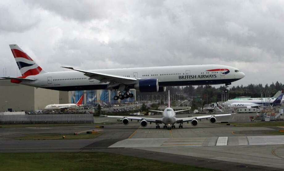 A British Airways Boeing 777 lands at Paine Field while Cargolux's first 747-8 Freighter waits on Oct. 12, 2011 in Everett, Wash. Photo: Aubrey Cohen