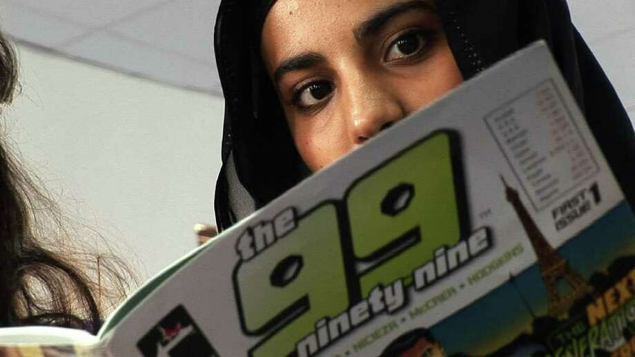 """A girl in Kuwait reads """"The 99"""" in her school's library. Photo: PBS"""
