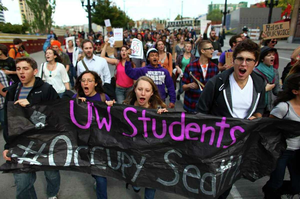 University of Washington students march down Pine Street as students from area high schools and colleges walked out of classes and joined protesters at the Occupy Seattle protest at Westlake Park on Wednesday, October 11, 2011 in Seattle. The protest at Westlake, organized in support of the Occupy Wall Street demonstration in New York, is its second week.