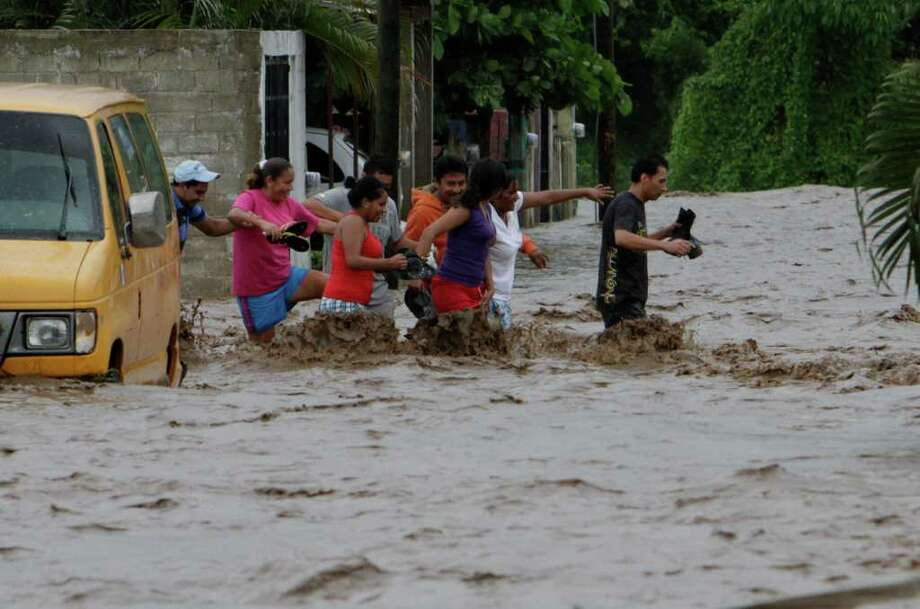 Residents wade through a flooded street in Villa de Coral, Mexico, Wednesday Oct. 12, 2011. Hurricane Jova slammed into Mexico's Pacific coast as a Category 2 storm early Wednesday, killing at least two people and injuring some six, while a tropical depression hit farther south and unleashed steady rains that contributed to 13 deaths across the border in Guatemala. Photo: Marco Ugarte, Associated Press / AP