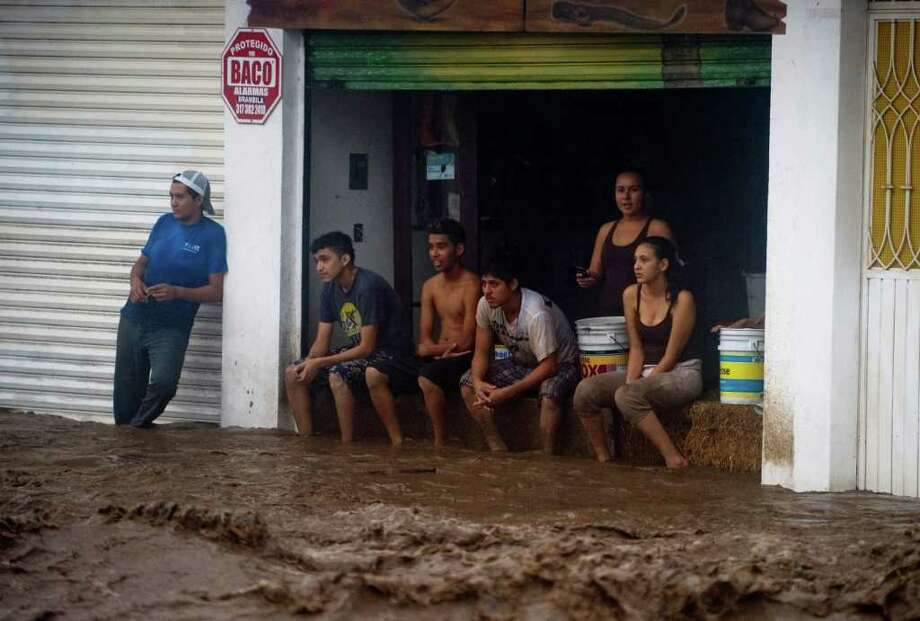 Locals stare at a flooded street in Manzanillo, Colima State, Mexico, on October 12, 2011. Jova lost its hurricane status, but remained a deadly threat as a tropical storm, dumping torrential rain across much of Mexico's Pacific coast and triggering flooding and power cuts. Photo: ALFREDO ESTRELLA, Getty / AFP