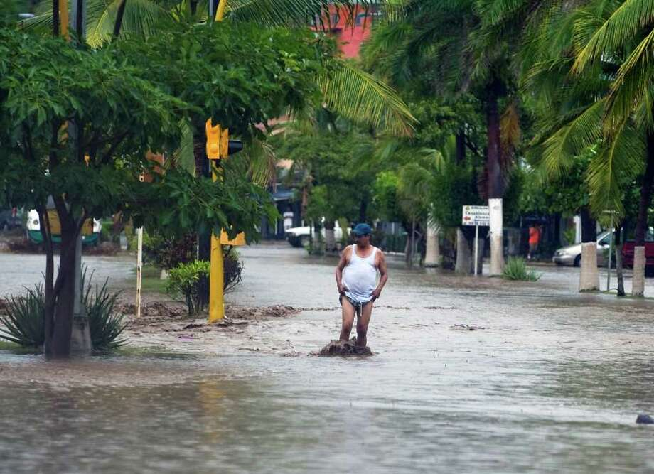 A man wades through a flooded street in Manzanillo, Colima State, Mexico, on October 12, 2011. Photo: ALFREDO ESTRELLA, Getty / AFP