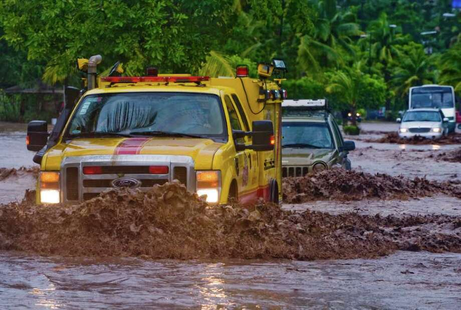 Trucks drive in a flooded street in Manzanillo, Colima State, Mexico, on October 12, 2011. Photo: ALFREDO ESTRELLA, Getty / AFP