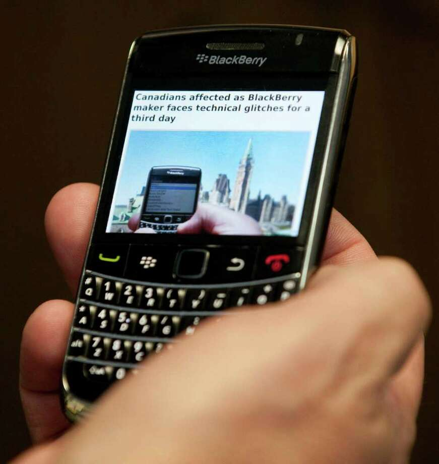 A Blackberry subscriber holds a Research in Motion Blackberry in Ottawa, Wednesday Oct.12, 2011. Sporadic outages of BlackBerry messaging and email service spread to the U.S. and Canada on Wednesday, as problems stretched into the third day for Europe, Asia, Latin America and Africa. (AP Photo/The Canadian Press, Adrian Wyld) Photo: Adrian Wyld, ASSOCIATED PRESS / AP2011