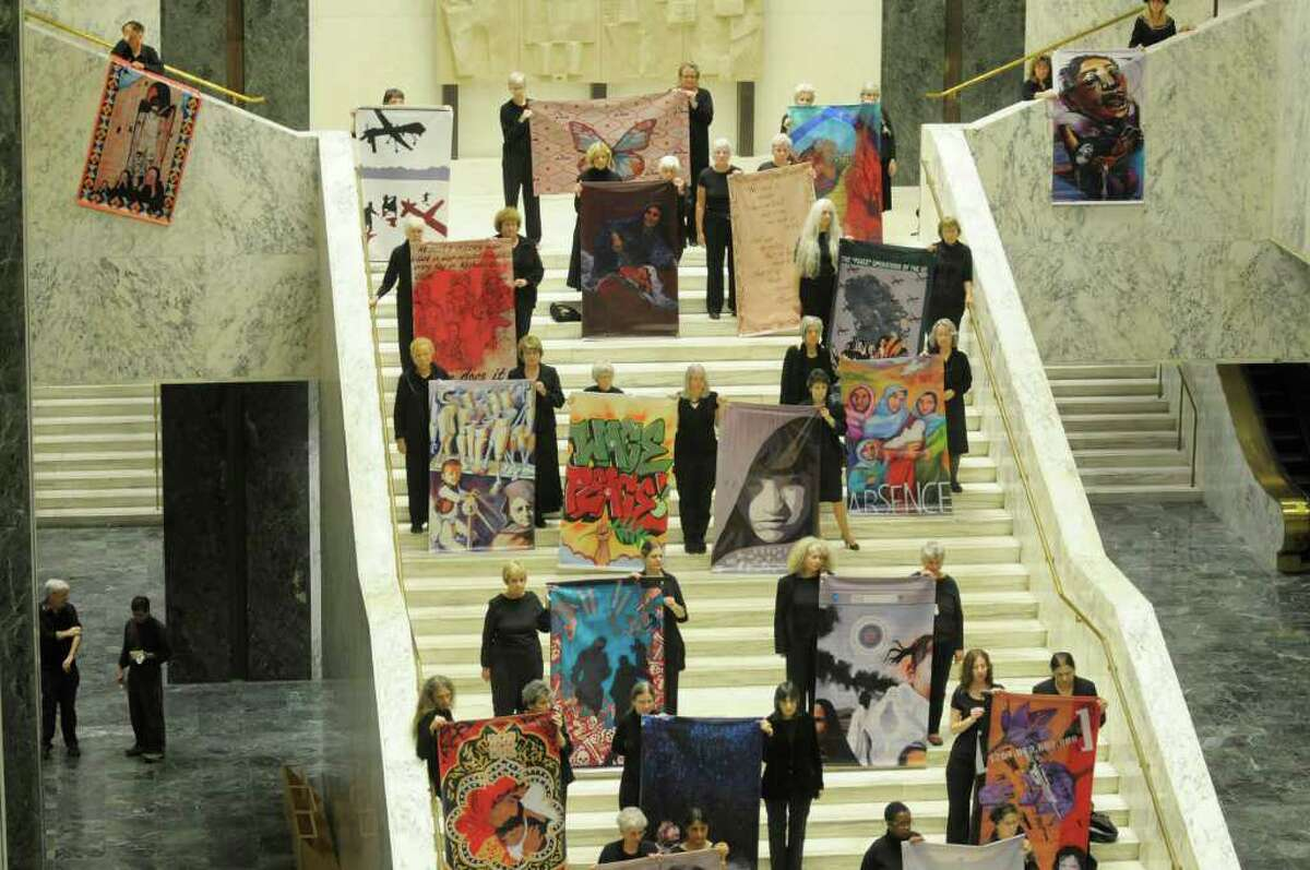 Women hold artwork done by various artists from around the country that reflect the agony and human cost of the Afghan War during a press event held by the organization Women Against War in the Legislative Office Building on Wednesday, Oct. 12, 2011 in Albany. The press event was held to announce the locations that the artwork will be displayed in the region. (Paul Buckowski / Times Union)