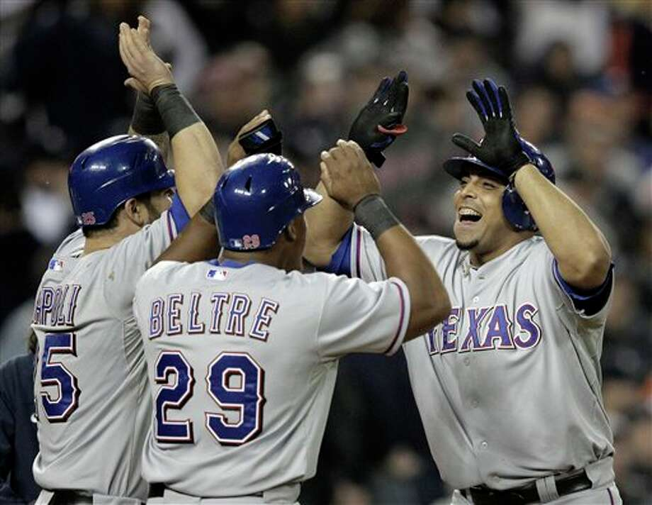 The Rangers' Adrian Beltre and Mike Napoli celebrate with teammate Nelson Cruz after his 3-run home run in the 11th inning in Game 4 of baseball's American League championship series against the Tigers on Wednesday Detroit. (AP Photo/Charlie Riedel)