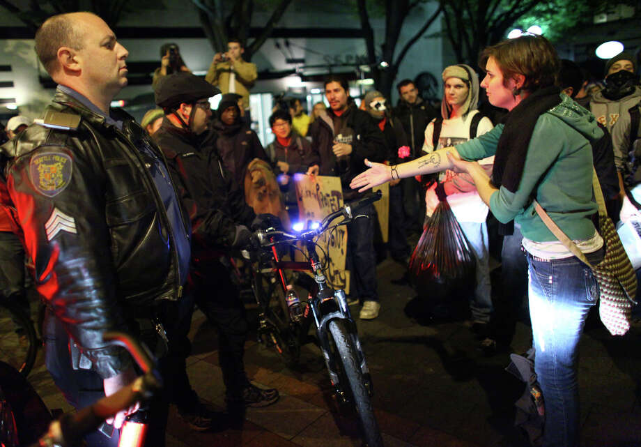 Occupy Seattle demonstrators confront police at Westlake Park on Wednesday in Seattle. Police ordered the protesters to clear the park at 10 p.m. About 150 refused the order, and two were arrested. Police pulled back after the arrests. Photo: JOSHUA TRUJILLO / SEATTLEPI.COM