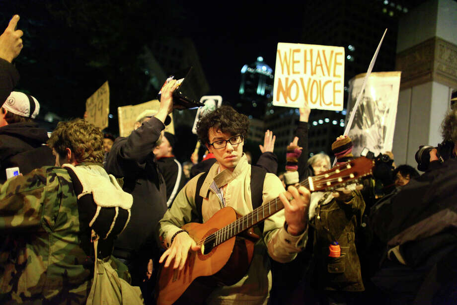 An Occupy Seattle demonstrator plays his guitar as an angry crowd yells at police at Westlake Park. Photo: JOSHUA TRUJILLO / SEATTLEPI.COM