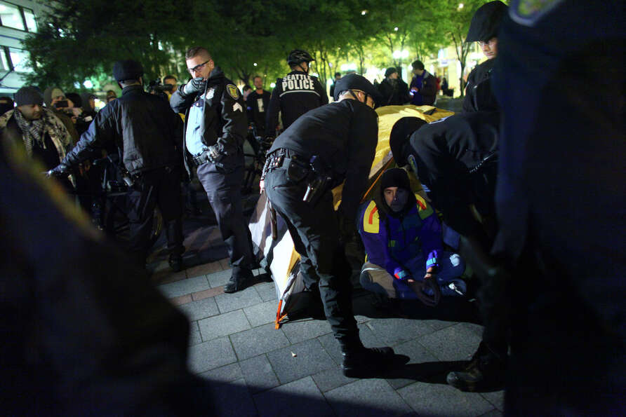 Seattle police officers speak to an Occupy Seattle demonstrator before arresting him at Westlake Par