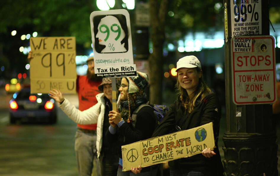 Occupy Seattle demonstrators holds signs for passing motorists at Westlake Park. Police ordered the