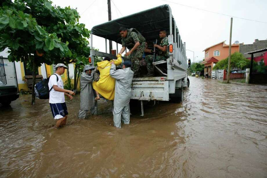 Soldiers evacuate people from a flooded area of Villa de Coral, Mexico, Wednesday Oct. 12, 2011. Hurricane Jova slammed into Mexico's Pacific coast as a Category 2 storm early Wednesday, killing at least two people and injuring some six, while a tropical depression hit farther south and unleashed steady rains that contributed to 13 deaths across the border in Guatemala. Photo: AP