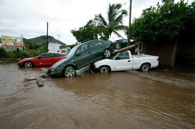 Cars pile up after being dragged by flood waters in Villa de Coral, Mexico, Wednesday Oct. 12, 2011. Hurricane Jova slammed into Mexico's Pacific coast as a Category 2 storm early Wednesday, killing at least two people and injuring some six, while a tropical depression hit farther south and unleashed steady rains that contributed to 13 deaths across the border in Guatemala. Photo: AP