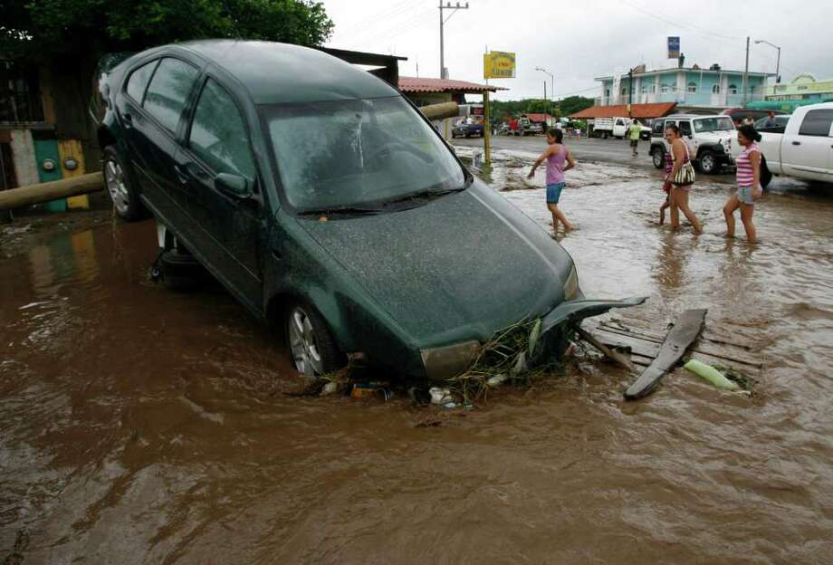 A car is seen after being dragged by flood waters in Villa de Coral, Mexico, Wednesday Oct. 12, 2011. Hurricane Jova slammed into Mexico's Pacific coast as a Category 2 storm early Wednesday, killing at least two people and injuring some six, while a tropical depression hit farther south and unleashed steady rains that contributed to 13 deaths across the border in Guatemala. Photo: AP