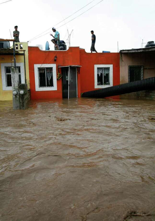 Residents walk on the roof of a house at a flooded street in Villa de Coral, Mexico, Wednesday Oct. 12, 2011. Hurricane Jova slammed into Mexico's Pacific coast as a Category 2 storm early Wednesday, killing at least two people and injuring some six, while a tropical depression hit farther south and unleashed steady rains that contributed to 13 deaths across the border in Guatemala. Photo: AP