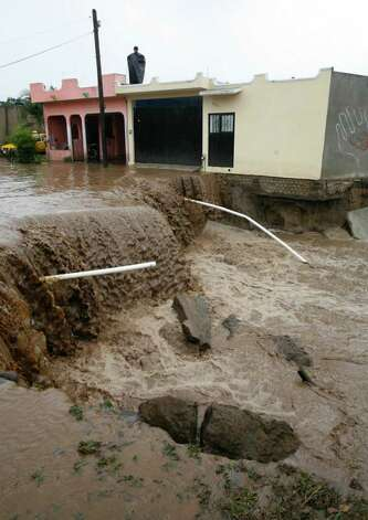 Flood water cascades down a street in Villa de Coral, Mexico, Wednesday Oct. 12, 2011. Hurricane Jova slammed into Mexico's Pacific coast as a Category 2 storm early Wednesday, killing at least two people and injuring some six, while a tropical depression hit farther south and unleashed steady rains that contributed to 13 deaths across the border in Guatemala. Photo: AP